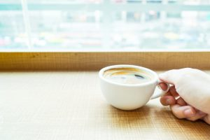 woman hand holding Espresso Coffee cup on wood table in cafe with blur city background, Leisure lifestyle concept.