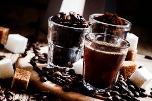 Three types of coffee: Grinded Arabica coffee beans, freshly brewed espresso, steel geyser coffee maker, vintage wooden background, selective focus